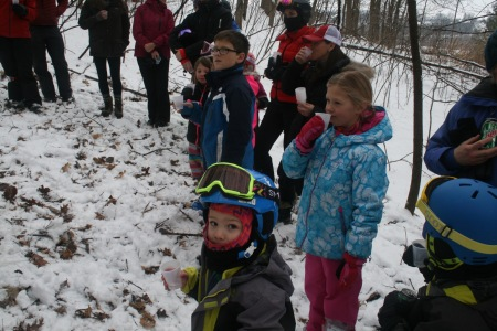 Kids enjoying a sample of sap and finished syrup