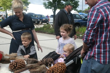 A young family checking out some North American animal hides and pine cones.
